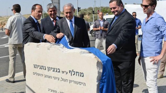 Le Premier ministre Benjamin Netanyahu, le ministre des Transports Yisrael Katz (à droite), le maire de Jérusalem Nir Barkat (à gauche) et le vice-maire de Jérusalem et président de la commission de planification et de construction de la ville Kobi Kahlon (2° à gauche) pendant la cérémonie d'inauguration du nouvel échangeur de la voie express Begin nommé Benzion Netanyahu, d'après le père décédé du Premier ministre, à l'ouest du quartier arabe de Beit Hanina, à Jérusalem, le 5 mai 2013. (Crédit : Kobi Gideon/GPO/Flash90)