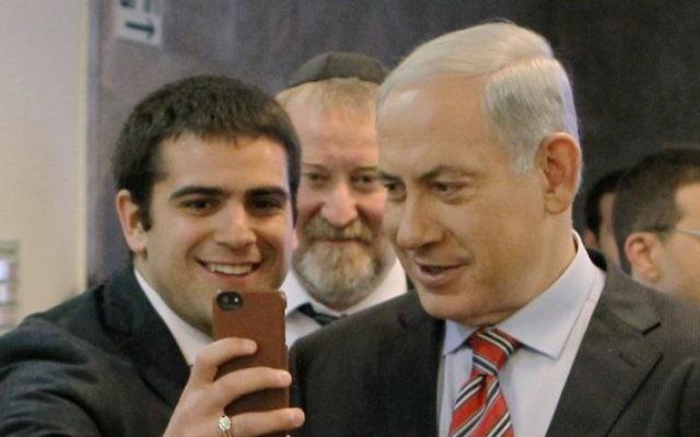 La Premier ministre Benjamin Netanyahu pose pour un selfie avec un étudiant le 30 mars 2014 (Danny Meron/POOL/Flash90)