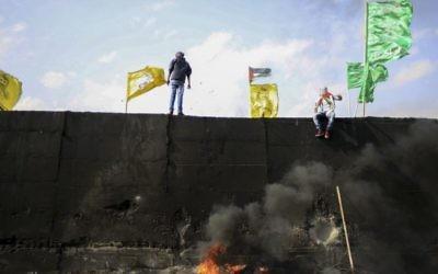 Drapeaux du Fatah, du Hamas et d'autres mouvements palestiniens au sommet de la barrière de sécurité de Cisjordanie, pendant une manifestation en novembre 2015. Illustration. (Crédit : Muammar Awad/Flash90)