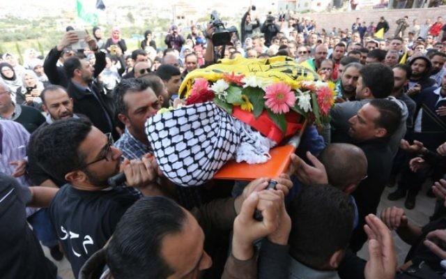 Des Palestiniens en deuil chantent des slogans pendant qu'ils transportent le corps de Mahmoud Shalan, 17 ans, pendant ses funérailles à Deir Debwan, un village de Cisjordanie proche de Ramallah, le 2 mars 2016. (Crédit : Flash90)