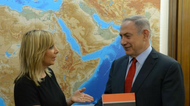 Le Premier ministre Benjamin Netanyahu reçoit le rapport de la Commission Palmor pour éradiquer le racisme dirigé contre les Israéliens éthiopiens de la directrice générale du ministère de la Justice, Emi Palmor, dans les bureaux du premier ministre à Jérusalem, le 31 juillet 2016. (Crédit : Amos Ben Gershom/GPO)