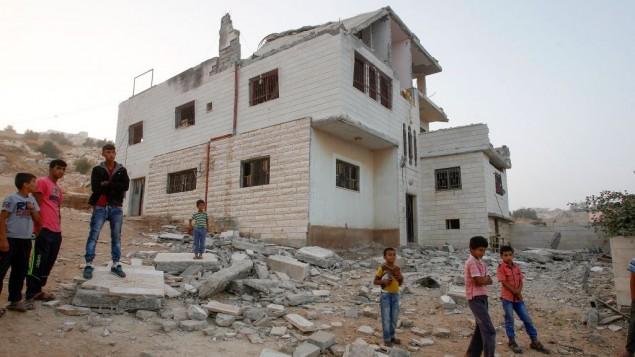 Des Palestiniens vérifient les dommages dans la maison de Mohammad Muhamra, terroriste du marché Sarona de Tel Aviv, après sa démolition par l'armée israélienne à Yatta, au sud de Hébron, le 4 août 2016. (Crédit : Wisam Hashlamoun/Flash90)
