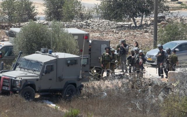 Les forces de sécurité israéliennes sur les lieux de la mort d'Iyad Hamad, Palestinien de 38 ans qui a été abattu par des soldats israéliens après avoir couru vers un poste de garde près de Silwad, en Cisjordanie, le 26 août 2016. (Crédit : Flash90)