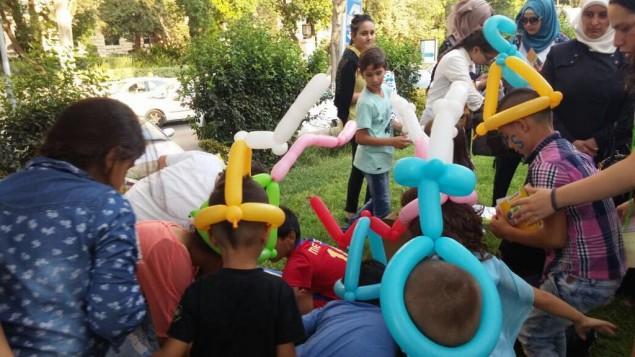 Des ballons sculptés en forme  de lettres arabes, latines et hébraïques pendant une fête de rentrée au YMCA de Jérusalem, le 29 août 2016. (Crédit : Dasee Berkowitz)