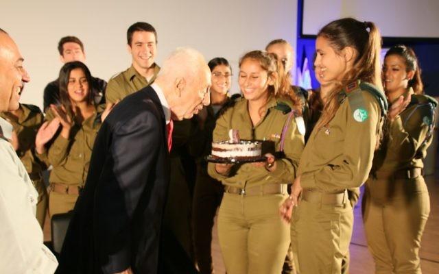 Shimon Peres (au centre),ancien président d'Israël, a fêté son 93e anniversaire entouré de Dror Shalom (à gauche), directeur de la division de recherche des renseignements militaires, et de soldats de cette division, le 2 août 2016. (Crédit : Yosef Angel)