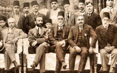 Sir Sassoon Eskell (au centre, avec un fez) est assis juste à côté du roi Faisal Ier d'Irak (avec une barbe noire) à Bagdad, dans les années 1920. (Crédit : WikiCommons)