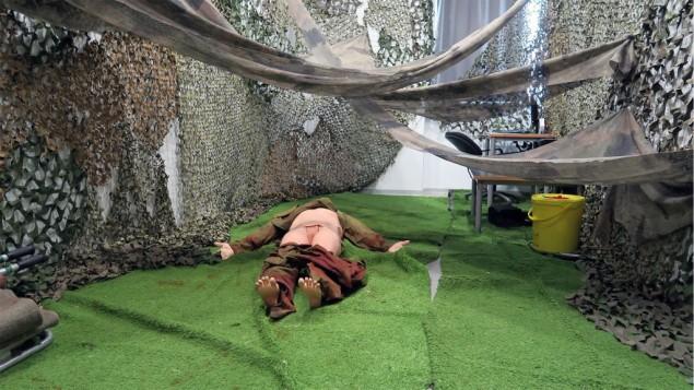 """Un mannequin dans l'une des """"pièces à une seule victime"""" du simulateur de traumatisme médical. La pièce imite un environnement forestier, où les soldats pourraient devoir travailler à quatre pattes. (Crédit : Luke Tress/Times of Israel)"""