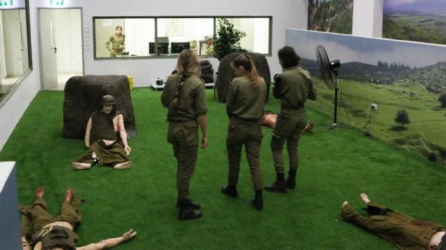 Les instructeurs du simulateur de traumatisme médical préparent un exercice dans la pièce d'évènement à victimes multiples. Ils peuvent suivre l'action depuis la pièce, ou depuis la salle d'observation dans le fond. (Crédit : Luke Tress/Times of Israel)