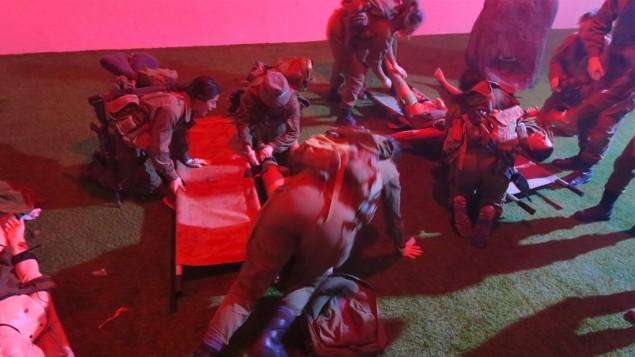Les infirmiers combattants en formation préparent l'évacuation de la salle d'évènement à victimes multiples. Les soldats doivent d'abord arrêter les hémorragies importantes, puis alignent les victimes au centre de la pièce pour être prêt à les évacuer. (Crédit : Luke Tress/Times of Israel)