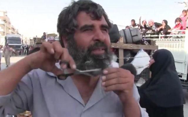 Un Syrien coupe sa barbe après que sa ville de Manbij a été libéré du contrôle de l'Etat islamique, le 13 août 2016 (Crédit : Capture d'écran / K24)