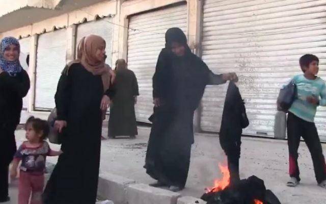 Une Syrienne brûle une burqa pour célébrer la libération de la ville de Manbij du contrôle de l'EI, le 13 août 2016. (Crédit : Capture d'écran / K24)
