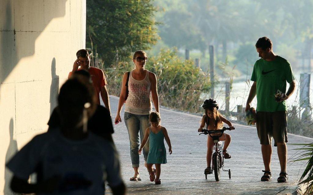 Les familles profitant d'une chaude journée d'été au Yarkon Park, Tel Aviv (Crédit : Moshe Shai / Flash90)