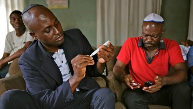 Le dirigeant spirituel de la communauté juive Beth Yeshourun, Serge Etele (à gauche) inspecte une nouvelle mezuza, chez la famille Ambomo, à Douala, au Cameroun, en février 2014. (Crédit : Jono David)