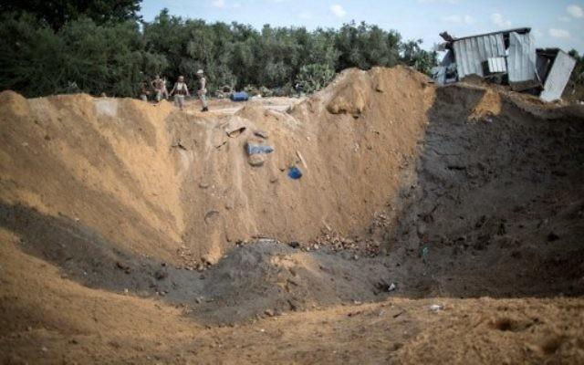 Des Palestiniens du mouvement du Jihad islamique arrivent pour inspecter un cratère à Beit Lahia dans le nord de la bande de Gaza, après un raid aérien israélien, le 22 août 2016.  (Crédit : Mahmud Hams/AFP)
