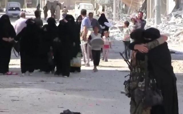 Une Syrienne étreint un combattant des Forces démocratiques syrienne après que la libération de la ville de Manbij du contrôle de l'EI, le 13 août 2016 (Crédit : Capture d'écran / K24)