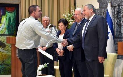 Le général Doron Piles (à gauche) serre la main du ministre de la Défense Avigdor Liberman pendant sa nomination comme nouveau président de la Cour d'appel militaire, en présence du président Reuven Rivlin, de la présidente de la Cour suprême Miriam Naor, et le chef d'Etat-major Gadi Eizenkot, le 15 août 2016. (Crédit : Ariel Hermoni/ministère de la Défense)