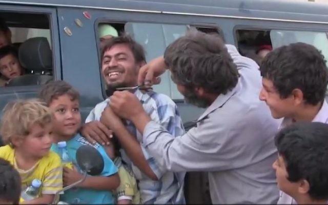 Un Syrien coupe la barbe d'un autre Syrien après que sa ville de Manbij a été libéré du contrôle de l'Etat islamique, le 13 août 2016 (Crédit : Capture d'écran / K24)