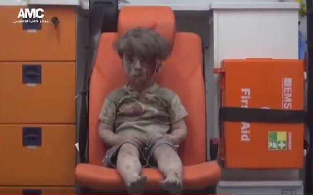 """Omran Daqneesh, 5 ans, après le bombardement de sa maison à Alep, le 17 août 2016. Sa photo a fait le tour du monde, et est, selon Washington, """"le vrai visage"""" du conflit. (Crédit : capture d'écran YouTube/BBC News)"""