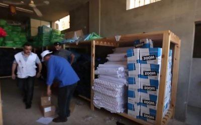 Une distribution de l'aide Save the Children distribution dans un entrepôt dans la bande de Gaza, en 2014 (Crédit : Save the Children / YouTube)