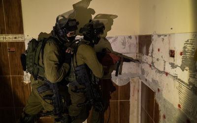Des soldats israéliens se préparent à démolir la maison de Mohammed Omaireh, qui a avoué faire partie de la cellule terroriste qui a tué le rabbin Miki Mark. Le bâtiment a été détruit dans le village de Dura, en Cisjordanie, le 30 août 2016. (Crédit : porte-parole de l'armée israélienne)