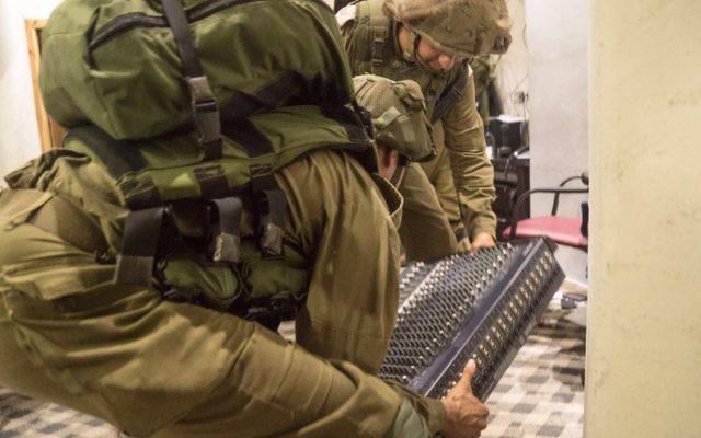 Des soldats israéliens démantèlent l'équipement de radio-transmission de la radio al-Sabanel, à Dura, près de Hébron, en Cisjordanie, le 31 août 2016. (Crédit : unité des porte-paroles de l'armée israélienne)