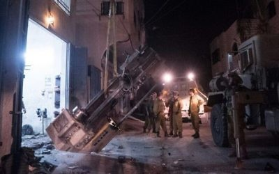 Les troupes de l'armée en train de sortir des machines à fabriquer des armes d'un atelier en Cisjordanie, le 1er Août 2016 (Crédit : Porte-parole de l'armée)