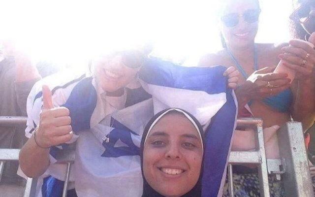 Doaa Elghobashy, joueuse olympique de beach-volley égyptienne, sourit sur une photo alors qu'une femme enveloppée dans le drapeau israélien est derrière elle, en août 2016. (Crédit : Facebook)