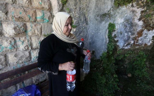 Une Palestinienne transporte des bouteilles remplies d'eau de source à Salfit, au nord de Ramallah, le 23 juin 2016. (Crédit : AFP/Jaafar Ashtiyeh)