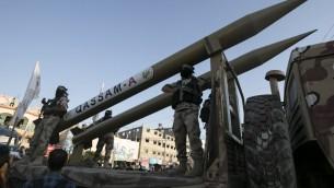 Des membres des Brigades al-Qassam, la branche armée du Hamas, présentent leurs roquettes Qassam pendant une cérémonie marquant le deuxième anniversaire de l'assassinat des commandants militaires du Hamas Mohammed Abu Shamala et Raed al-Attar lors d'une parade militaire anti-Israël à Rafah, dans le sud de la bande de Gaza, le 21 août 2016. (Crédit : Saïd Khatib/AFP)