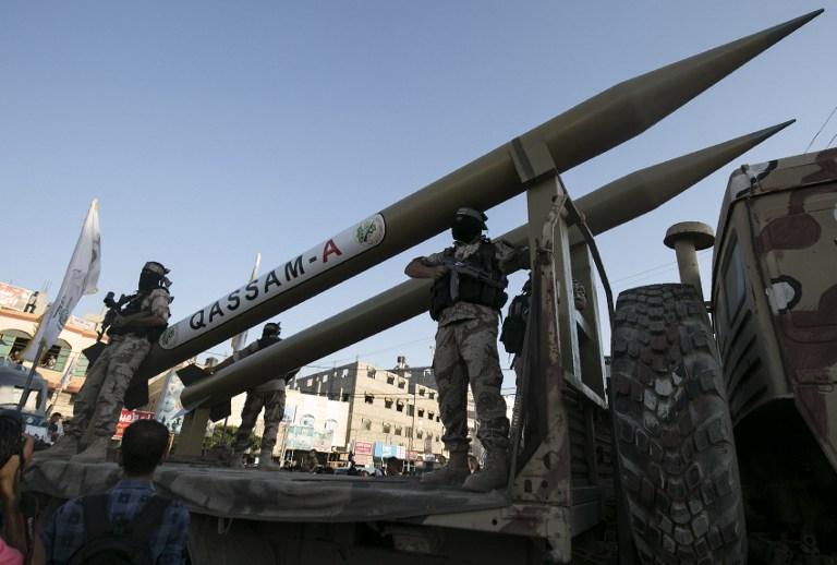 Des membres des Brigades Ezzedine al-Qassam, la branche armée du Hamas, devant leurs roquettes Qassam pendant une cérémonie marquant le deuxième anniversaire de l'assassinat des commandants militaires du Hamas Mohammed Abu Shamala et Raed al-Attar lors d'une parade militaire anti-Israël à Rafah, dans le sud de la bande de Gaza, le 21 août 2016. (Crédit : Saïd Khatib/AFP)