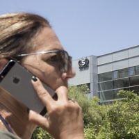 Une Israélienne utilise son iPhone face au bâtiment abritant le firme de cyber-sécurité israélienne NSO Group, le 28 août 2016 à Herzliya. (Crédit : AFP Photo / Jack Guez)
