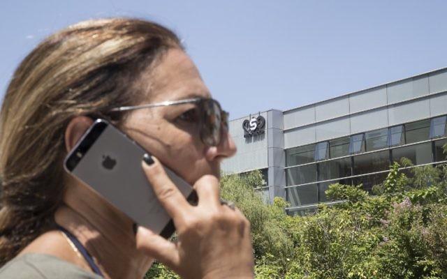 Une Israélienne utilise son iPhone en face du bâtiment abritant le firme de cyber-sécurité israélienne NSO Group, le 28 août 2016 Herzliya, à Tel Avi. (Crédit : AFP Photo / Jack Guez)
