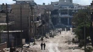 Des combattants syrien pro-régime dans les rues de Ramussa, après leur prise de contrôle d'un district stratégiquement important dans la banlieue d'Alep la veille, le 9 septembre 2016. (Crédit : AFP/George Ourfalian)