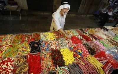Un Palestinien achète des bonbons pendant la préparation des magasins musulmans à la fête de l'Aïd al-Adha, sur le marché de la Vieille Ville de Jérusalem, le 11 septembre 2016. (Crédit : AFP/Hazem Bader)