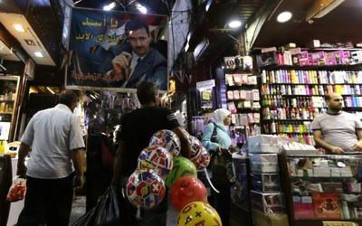 """Une affiche du président syrien Bashar el-Assad disant """"Assad est avec vous pour toujours"""" au marché populaire Hamidiyeh de la vieille ville de Damas, pendant les préparatifs de l'Aïd al-Adha, le 11 septembre 2016. (Crédit : AFP/Louai Beshara)"""