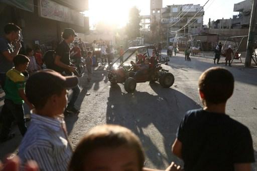 Des enfants syriens jouent dans la rue au troisième jour de l'Aïd al-Adha, dans la ville contrôlée par les rebelles de Hamouria, près de Damas, au deuxième jour d'un cessez-le-feu, le 14 septembre 2016. (Crédit : AFP/Abd Doumany)