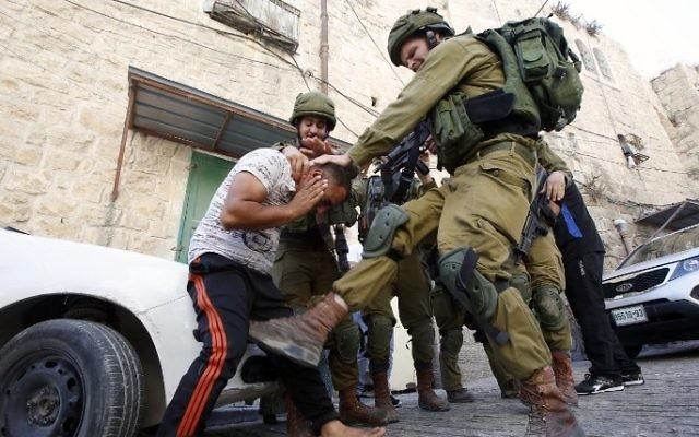 Un soldat israélien donne un coup de pied à un Palestinien pendant son arrestation à Hébron, en Cisjordanie, le 20 septembre 2016. (Crédit : AFP/Hazem Bader)