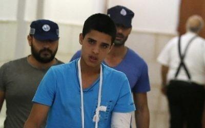 Ahmed Manasra (au premier plan), adolescent palestinien de 14 ans, a été jugé coupable de tentative de meurtre à l'encontre de deux jeunes Israéliens pendant une attaque au couteau en octobre 2015, à sa sortie du tribunal de Jérusalem, le 25 septembre 2016. (Crédit : Ahmad Gharabli/AFP)