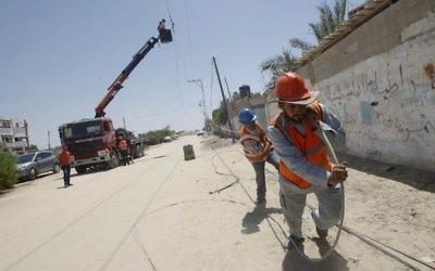 Des employés de la compagnie d'électricité palestinienne traînent une ligne électrique, à Rafah, dans le sud de la bande de Gaza, le 6 août 2014. (Crédit : Said Khatib/AFP)