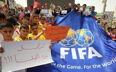 """De jeunes Palestiniens avec des cartons rouges et des pancartes """"Israël en-dehors de la FIFA"""" pendant une manifestation contre la Fédération israélienne de football à Hébron, en Cisjordanie, le 28 mai 2015. (Crédit : AFP/Hazem Bader)"""