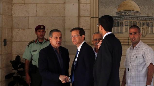 Nabil Abu Rudeineh (à gauche), porte-parole du président de l'Autorité palestinienne Mahmoud Abbas, accueille le chef de l'opposition israélienne, Isaac Herzog (au centre), au siège de l'AP à Ramallah, en Cisjordanie, le 19 août 2015. (Crédit : AFP/Abbas Momani)