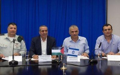 De gauche à droite, le directeur du COGAT, Yoav Mordechai, le ministre palestinien des Affaires étrangères, Hussein al-Sheik, le ministère israélien des Finances Moshe Kahlon et son directeur général Shai Babad signent un accord de résolution de la dette palestinienne électrique de deux milliards de shekels, le 12 septembre 2016. (Crédit : Facebook/COGAT)