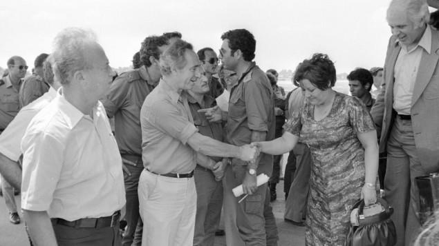 Shimon Peres, alors ministre de la Défense, avec l'ancien Premier ministre Yitzhak Rabin, rencontre les otages libérés d'Entebbe à leur atterrissage en Israël, le 4 juillet 1976. (Crédit : Uri Herzl Tzchik/unité des porte-paroles de l'armée israélienne/archives du ministère de la Défense)