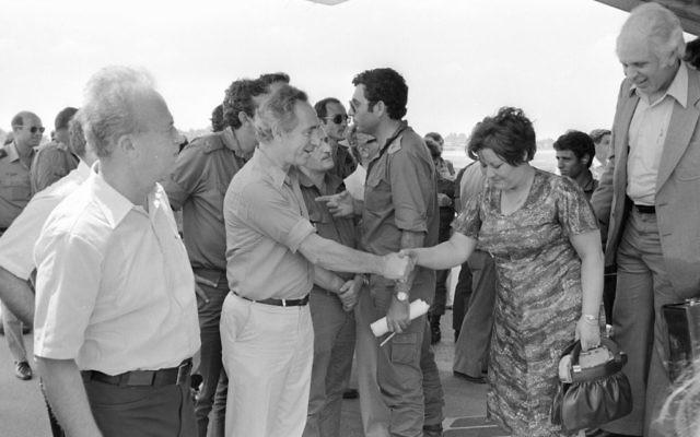 Shimon Peres, alors ministre de la Défense, et l'ancien Premier ministre Yitzhak Rabin, rencontrent les otages libérés d'Entebbe à leur atterrissage en Israël, le 4 juillet 1976. (Crédit : Uri Herzl Tzchik/unité des porte-paroles de l'armée israélienne/archives du ministère de la Défense)