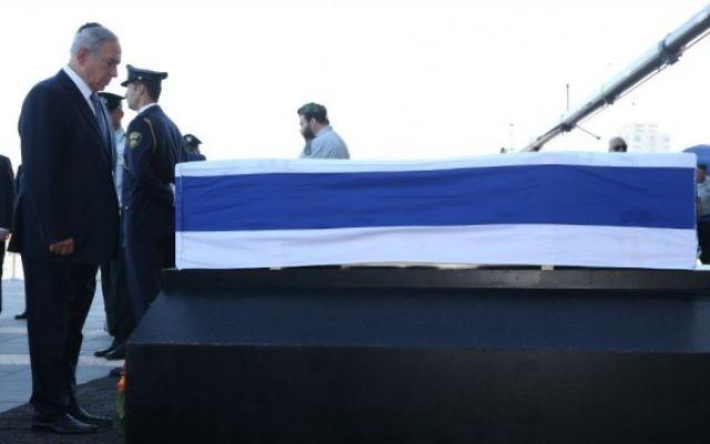 Benjamin Netanyahu se recueille sur le cercueil de Shimon Peres, le 29 septembre 2016 sur le parvis de la Knesset (Crédit :  bureau de Yizhak Harari / Knesset porte-parole)