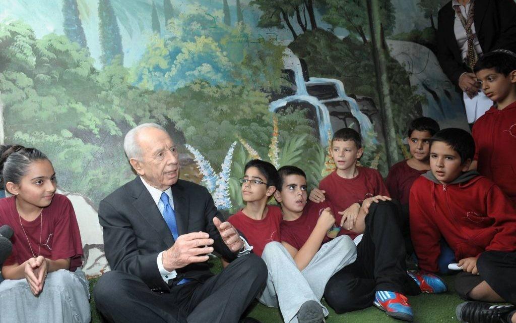 Shimon Peres, alors président, avec les enfants de Sderot dans un abri anti-bombes pendant l'opération Bordure protectrice, à l'été 2014. (Crédit : GPO)