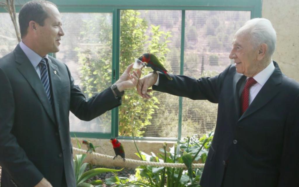 Shimon Peres, alors président, et le maire de Jérusalem, Nir Barkat (à gauche) avec des perroquets au Zoo biblique de la capitale, le 2 juillet 2013. (Crédit : Miriam Alster/Flash90)