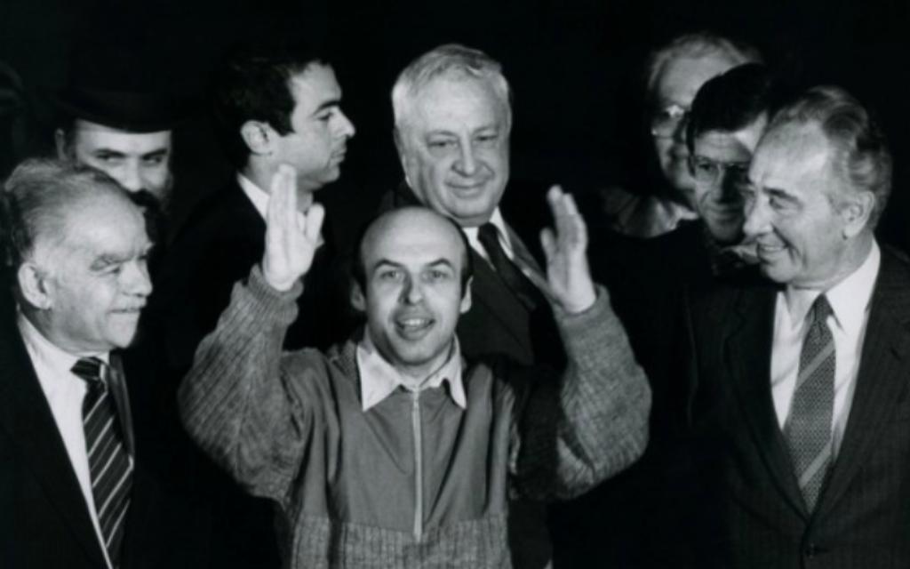 L'ancien prisonnier soviétique de Sion Natan Sharansky avec le Premier ministre Shimon Peres (d), ministre des Affaires étrangères Yitzhak Shamir (g) et Ariel Sharon (en arrière-plan), après sa sortie de prison en Union soviétique, à son arrivée en Israël le 11 février 1986. (Moshe Shai / FLASH90)