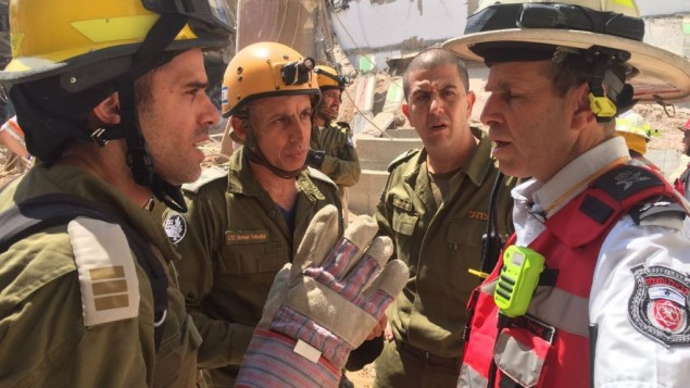 Les représentants de l'unité de secours et de recherche du Commandement de la Défense passive de l'armée israélienne avec le responsable des pompiers de Tel Aviv, Eyal Caspi (à droite), sur le site de l'effondrement d'un parking dans le quartier Ramat HaHayal, dans le nord de Tel Aviv, tuant au moins deux personnes, le 5 septembre 2016. (Crédit : unité des porte-paroles de l'armée israélienne)