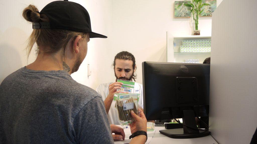 Un pharmacien de Tikkun Olam donne sa dose mensuelle de marijuana médicale à un patient au dispensaire de Tel Aviv, le 1er septembre 2016. (Crédit : Melanie Lidman/Times of Israel)